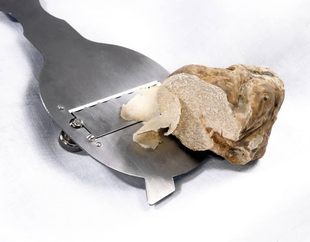 Mit dem Trüffelhobel werden weiße Trüffel in feine Scheiben geschnitten.
